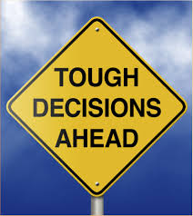 "The image displays a standard yellow sign reading ""Tough Decisions Ahead"" against a blue sky indicating that an effective approach for making tough decisions lies ahead."
