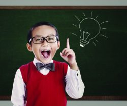 Image of a child in front of a chalkboard with a light bulb drawn on it. The light bulb symbolizes the child having an idea.