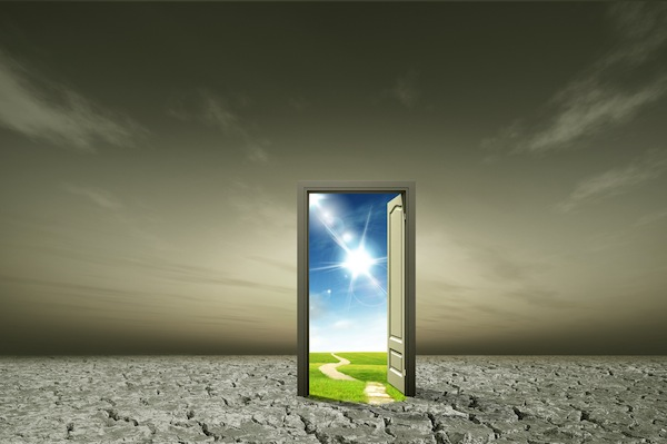 Image of a dark gray background with a door in the middle. The door is opening to a peaceful sunny day to illustrate a change in perception.