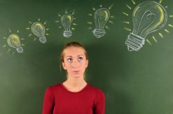 Image of female student standing in front of a chalkboard. There are images of four light bulbs over her head, from small to big, showing her ideas growing.