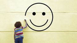 Image of a child drawing a big happy face on a wall.