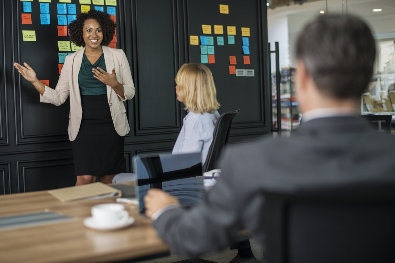 Image of a woman presenting in a business meeting