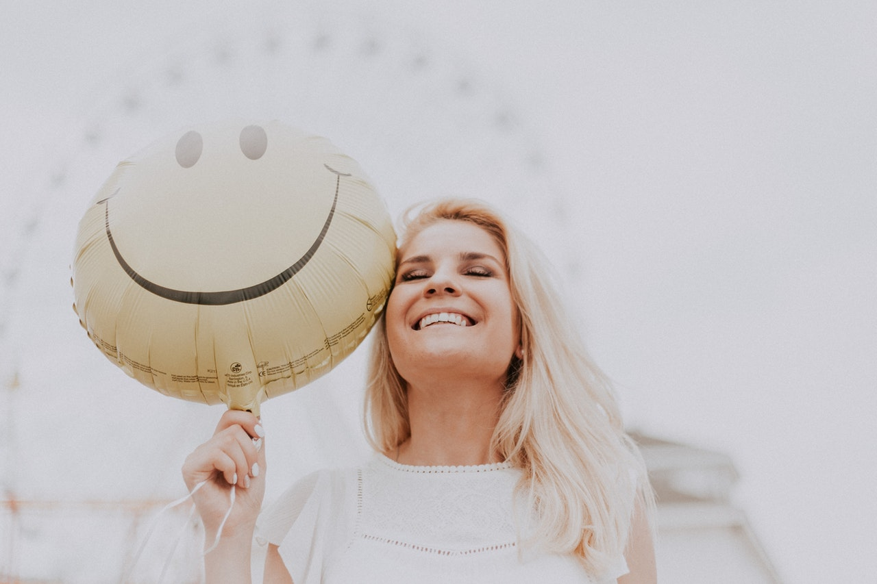 Image of a happy woman holding a balloon with a happy face - Positivity