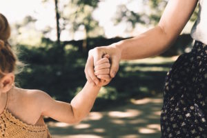 Image of an adult holding a child's hand